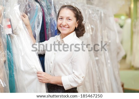 Smiling mature woman looking evening dress at boutique
