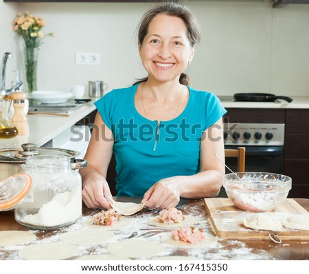 Smiling mature woman making meat dumplings (pelmeni)  at domestic kitchen - stock photo