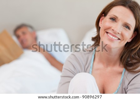Smiling mature woman on the bed with reading husband behind her