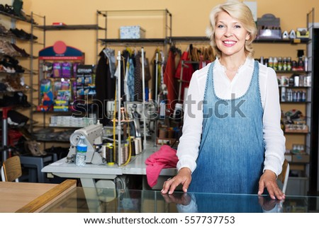 Smiling mature woman tailor standing in sewing workshop