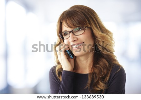 Smiling mature woman talking on phone in office - stock photo