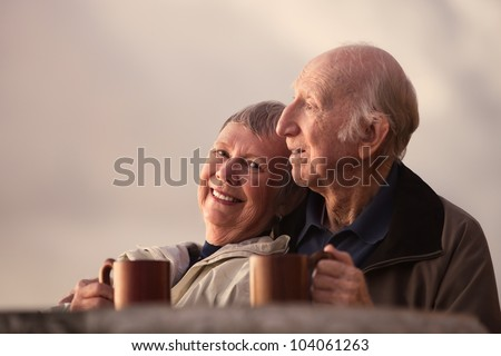 Smiling mature woman with husband in outdoors scene