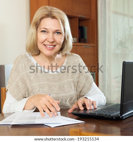 Smiling mature woman with laptop and financial documents at home interior