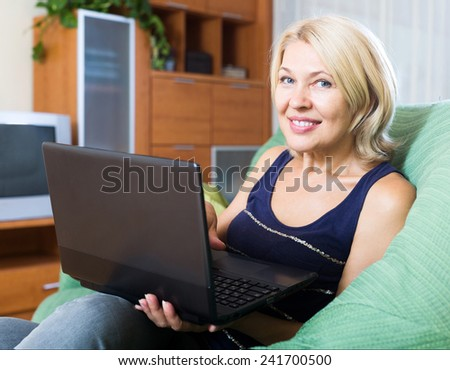 Smiling mature woman working on a laptop at her home