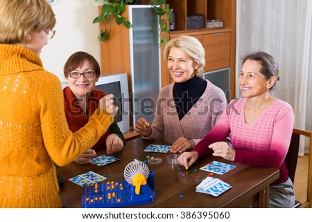 Smiling mature women having fun with table game indoor