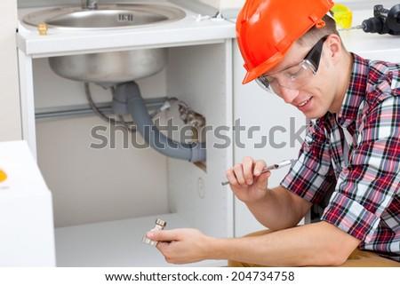 smiling mechanic adjusts the key near the kitchen sink - stock photo