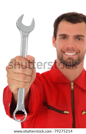 Smiling mechanic holding wrench. Selective focus on hand in foreground. All on white background. - stock photo