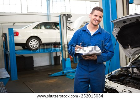 Smiling mechanic looking at camera at the repair garage - stock photo