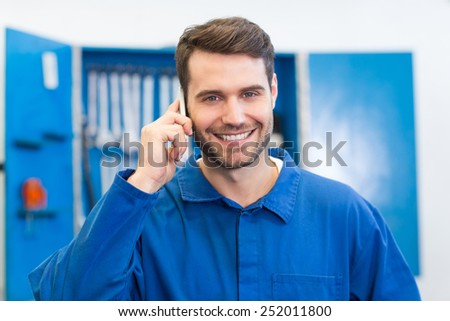 Smiling mechanic on the phone at the repair garage - stock photo