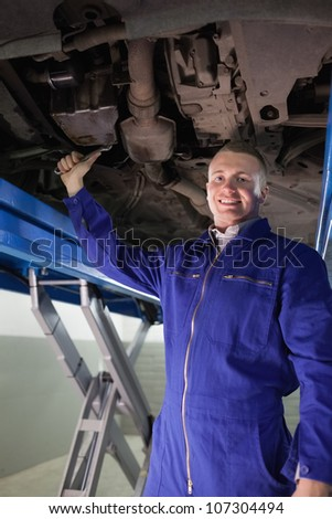 Smiling mechanic repairing with a spanner the below of a car in a garage