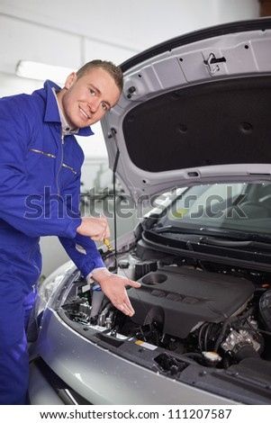 Smiling mechanic showing an engine in a garage