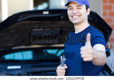 Smiling mechanic thumbs up - stock photo