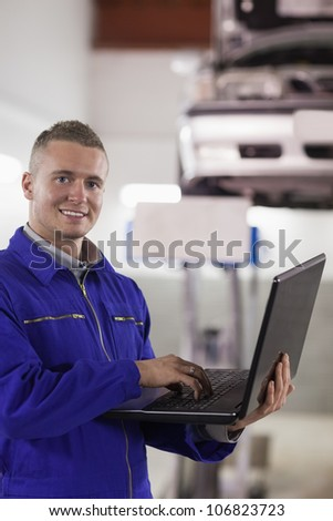 Smiling mechanic typing on a laptop in a garage
