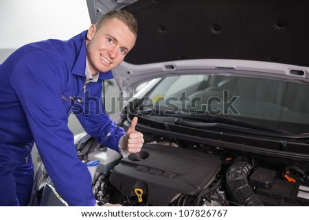 Smiling mechanic with his thumb up in a garage