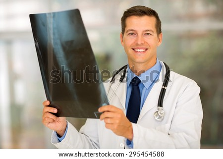 smiling medical doctor holding patient's x ray in office - stock photo