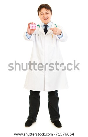 Smiling  medical doctor pointing finger on pack of pills isolated on white
