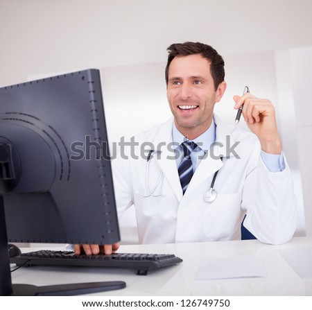Smiling Medical Doctor With Stethoscope Sitting At A Desk - stock photo