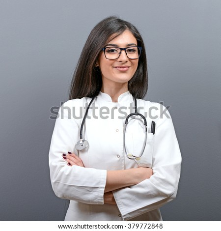 Smiling medical doctor woman with stethoscope against gray background - stock photo