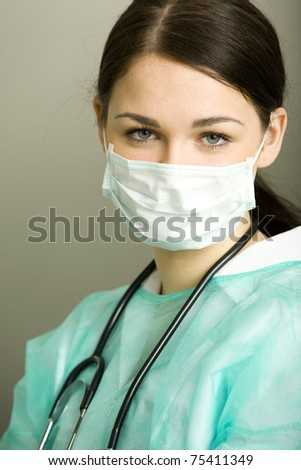 Smiling medical doctor woman with stethoscope, mask and other medical equipment