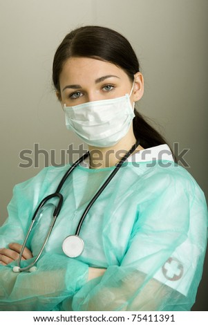 Smiling medical doctor woman with stethoscope, mask and other medical equipment - stock photo