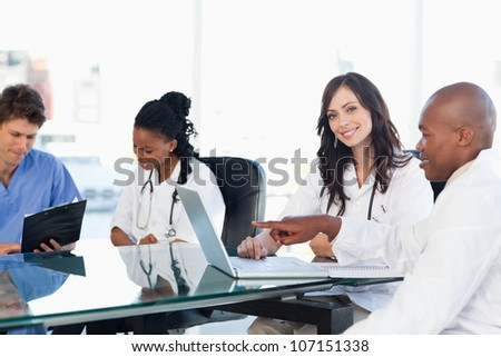 Smiling medical interns working on the computer near co-workers