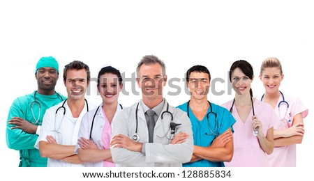 Smiling medical team standing arms crossed in line on white background - stock photo