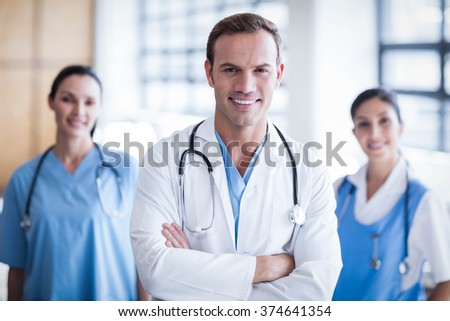 Smiling medical team with arms crossed in the hallway - stock photo
