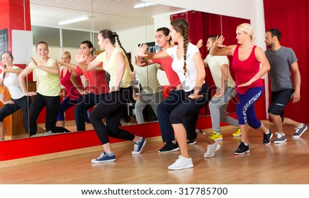 Smiling men and women dancing in a gymnastics class on a choreography intensive course - stock photo