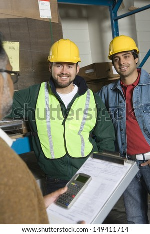 Smiling men in hardhats looking at cropped senior in the factory - stock photo