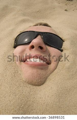 Smiling men in sand - stock photo