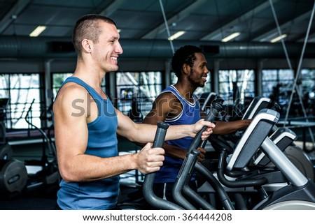 Smiling men using elliptical machine at gym - stock photo