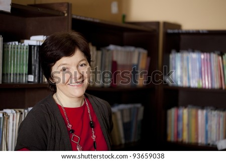Smiling mid-adult woman in the library. Professor, mature student, or librarian