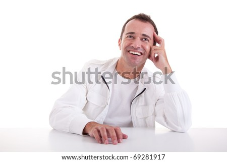 smiling middle-age man sitting at desk on a white background. Studio shot - stock photo