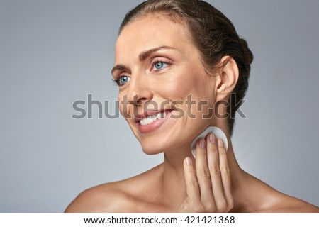 Smiling middle age woman wiping cleaning her face with cotton wool, wellness beauty skin care concept