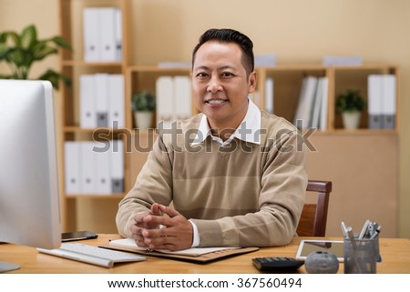 Smiling middle-aged businessman sitting at his table - stock photo
