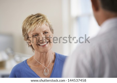 Smiling middle aged businesswoman discussing with male colleague in office - stock photo