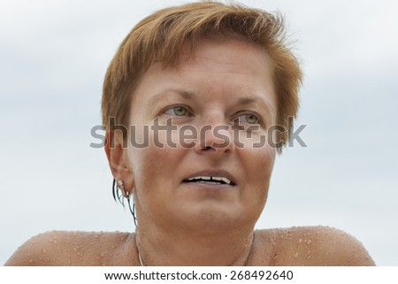 smiling middle aged caucasian tanned naked woman outdoor portrait after sea bathing - stock photo