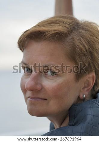 smiling middle aged caucasian tanned woman outdoor portrait - stock photo