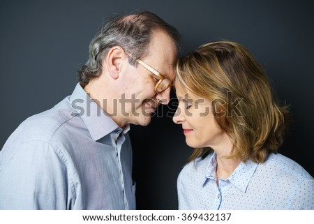 smiling middle-aged couple holding their foreheads together with eyes closed
