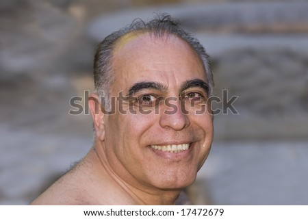 smiling middle-aged Iranian man looking over shoulder in closeup
