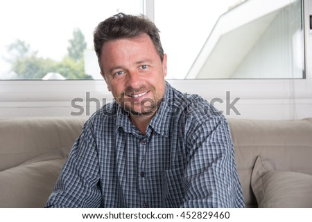 Smiling middle-aged man, close up view in living room - stock photo