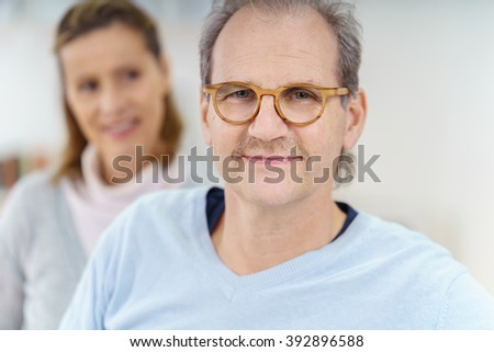 Smiling middle aged man with brown eyeglasses sitting in front of beautiful woman out of focus behind him