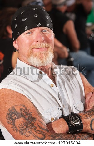 Smiling middle aged motorcycle gang man with folded arms - stock photo