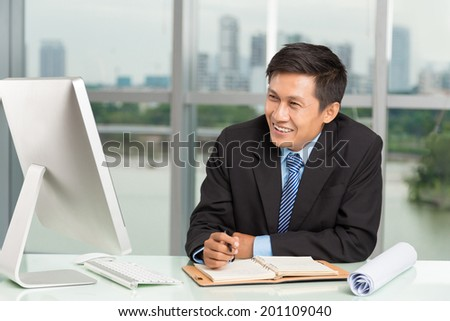 Smiling middle-aged Vietnamese businessman working on the computer at the office - stock photo