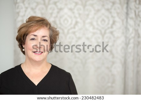Smiling middle aged white woman with copy space on right.