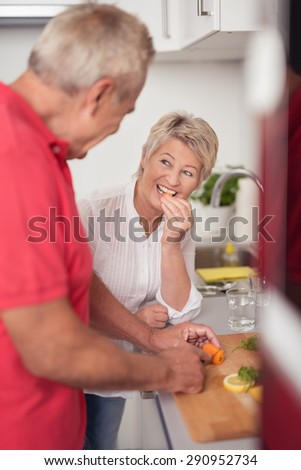 Smiling Middle Aged Wife Talking to her Husband While Preparing Food for Dinner at the Kitchen. - stock photo