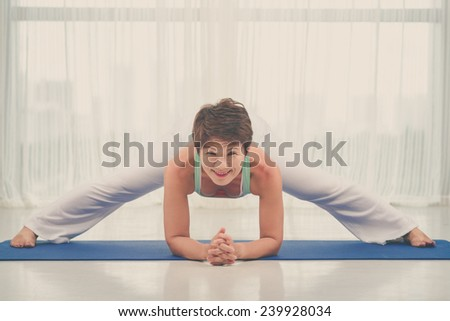 Smiling middle-aged woman doing splits and looking at the camera - stock photo
