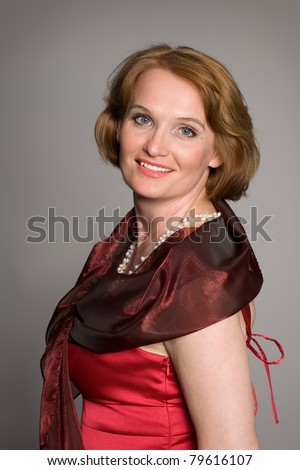 Smiling middle aged woman in a red dress. - stock photo