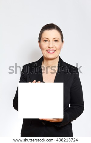 Smiling middle aged woman in black business outfit holding up a white card or placard, light background, empty copy or text space - stock photo