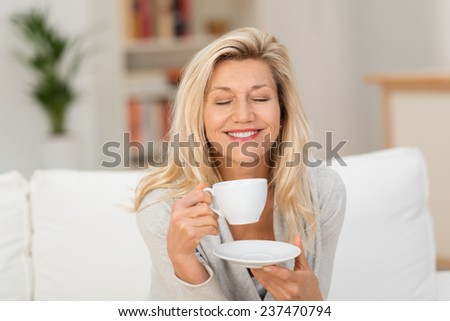 Smiling middle-aged woman savouring her coffee sitting holding a cup and saucer on her sofa with her eyes closed and smile of bliss